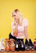 attractive blonde choosing shoes - stock photo