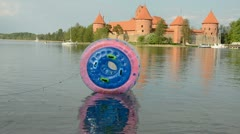 Zorbing ball on the lake water and Trakai castle Stock Footage