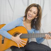 indian woman playing acoustic guitar - stock photo