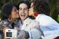 Man taking photograph of two women kissing him Stock Photos