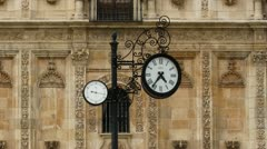 Clock against baroque bulding and people walking. Zoom out - Zoom in. Time Lapse - stock footage