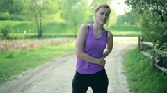 Young woman feeling pain in back during exercise HD Stock Footage