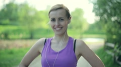 Portrait of young happy attractive female jogger in the park HD Stock Footage