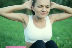 Young woman doing sit-ups, exercising in the park NTSC Stock Footage