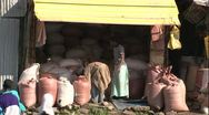 Stock Video Footage of Addis Ababa, Grain Market 2 men moving bags in stall WIDE