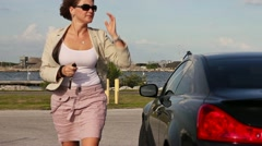 Woman exits car & walks out of frame towards camera Stock Footage