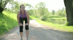Young blond woman taking breath after jogging HD - stock footage