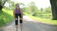 Stock Video Footage of Young blond woman taking breath after jogging HD