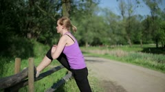 Attractive young sportswoman stretching leg along the fence HD Stock Footage