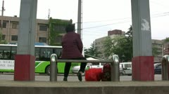 An old woman waits for the bus in China Stock Footage