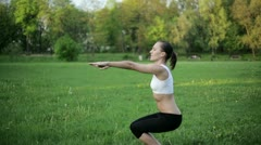 Woman in sport outfit doing a squat exercise  HD Stock Footage