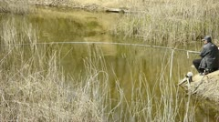 Fisherman fishing by the lake.river reeds in wind,shaking wilderness.elderly,le Stock Footage