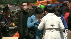 Three girls are enjoying a snack at a local Chinese market - stock footage
