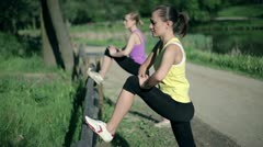 Two attractive young sportswomen stretching legs along the fence HD Stock Footage