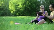 Two young sporty women with tablet computer outdoors, tracking shot  HD Stock Footage
