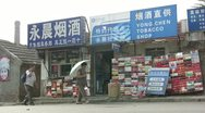 Stock Video Footage of People walk past a tobacco shop in the backstreets of a Chinese city
