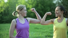 Portrait of two fit young women flexing her biceps, tracking shot HD Stock Footage