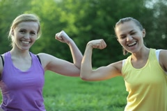 Portrait of two fit young women flexing her biceps, tracking shot NTSC - stock footage
