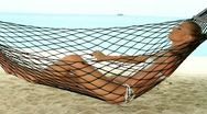 Attractive woman relaxing in a hammock Stock Footage