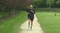 Older man running towards camera in slow motion Stock Footage