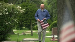 Older man walking through cemetery holding US flag Stock Footage