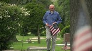Stock Video Footage of Older man walking through cemetery holding US flag