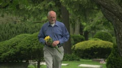 Older man walking through cemetery holding flowers - stock footage