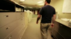 Man looking through file cabinets Stock Footage