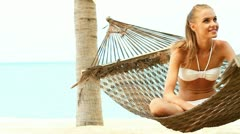 Beautiful smiling woman with long blonde hair sitting cross legged in a hammock  - stock footage