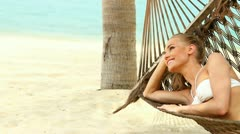 Happy young woman relaxing in a hammock Stock Footage