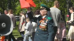 Victory Day. Veteran with a lot of medals keeps the red flag - stock footage