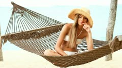 Pretty woman sitting on hammock at the beach - stock footage