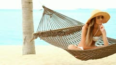 Happy woman on hammock at the exotic beach - stock footage