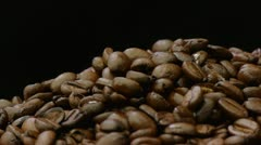 A pile of roasted coffee beans rotating on black background. Seamless loop. Stock Footage
