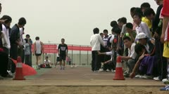 Chinese student at a long jump competition - crowd cheering him on Stock Footage