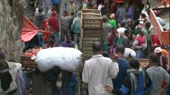Zoom out above crowded African city market, men walking carry heavy loads Stock Footage