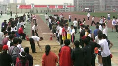 Students take part in a long jump competition in China Stock Footage