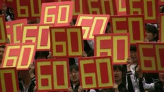 Chinese students holding up signs that read '60' (sixty) Stock Footage