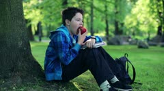 Young boy sitting by tree and eating apple in the park HD Stock Footage