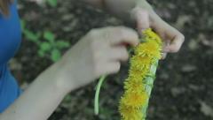 Woman weaves a wreath of dandelions  3 Stock Footage