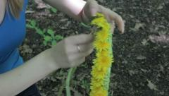 Woman weaves a wreath of dandelions Stock Footage