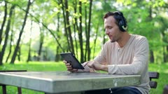 Happy young man watching movie on tablet computer in the park HD - stock footage