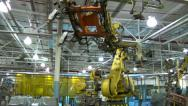 Stock Video Footage of Robotic Arm Swings Car Door Frame Around To Be Welded