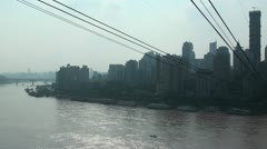 Commuting passengers use cable car over Yangtze river, Chongqing skyline China Stock Footage