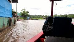 Traveling via boat along a river and through villages in Amazonia, Peru - stock footage