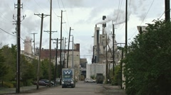 Truck Hauling Out of Busy Industrial Mill Complex Stock Footage