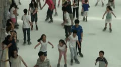 Kids are ice skating at a rink in a Chinese shopping mall Stock Footage