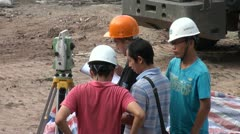 Young Chinese engineers are discussing measurements at construction site - stock footage