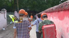 Chinese engineers walk through the streets carrying their equipment Stock Footage