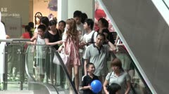 Shoppers using escalators in a mall in Guangzhou, China Stock Footage